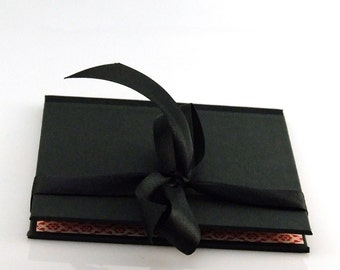 black DVD folio with elegant satin ribbon and red lining, CD packaging