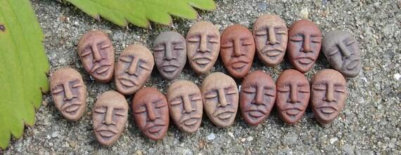 Many tiny stoneware faces - beads