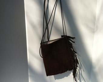 Pouch cross body bag small brown suede lined w/frang on side.