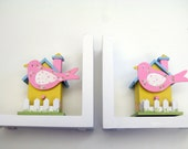Birds in a bird house hand painted bookends in pink, yellow and blue