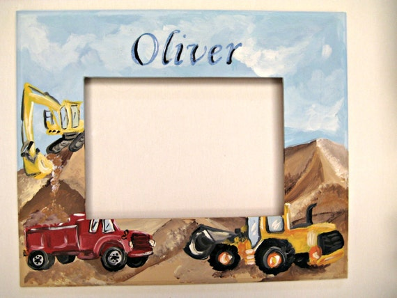 A hand painted personalized frame with a dump truck and a digger in piles of dirt