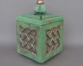 Blue-green stoneware box with gold Celtic knot, carved knob on lid, topped with a gold button