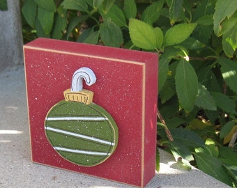 Green round ornament on red block for Christmas, Noel, shelf, desk, office, mantle and home decor