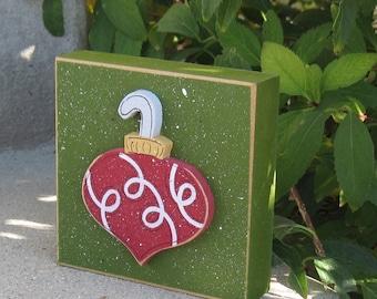 Red ornament on green block for Christmas, Noel, shelf, desk, office, mantle and home decor