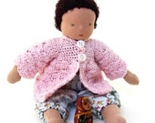 Waldorf inspired baby doll with brown hair green eyes and a pink jacket