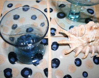 Set of four stoneware coasters with polka dot pattern. Blue, white, tan, matte.