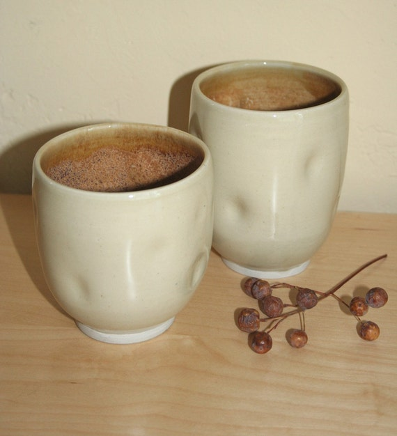 Pair of altered stoneware cups in natural celadon and honey