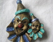Metal double clown face pin brooch with blue and seafoam green glittery trim