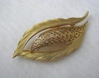 Gold tone vintage leaf brooch pin with open center design.