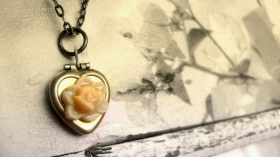 a very romantic heart locket with a lovely beige flower necklace