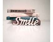 Smile in cursive, golden wood book lean