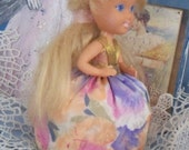 Tiny blonde doll with silky colorful skirt, recycled into a pin cushion one of a kind