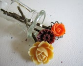 A trio of vintage inspired hair pins in creamy yellow, bright tangerine and warm burgundy