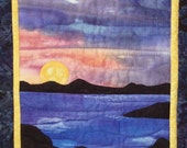 Quilted wall hanging -- A Peace Sign Sun is Setting Against a Handpainted Sky and Water with Shadowed Islands