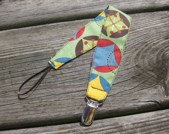 Universal Pacifier Clip - Green Starburst Hooty Hooty - Green Background with Blue, Yellow, Red, and Brown Circles and Diamonds