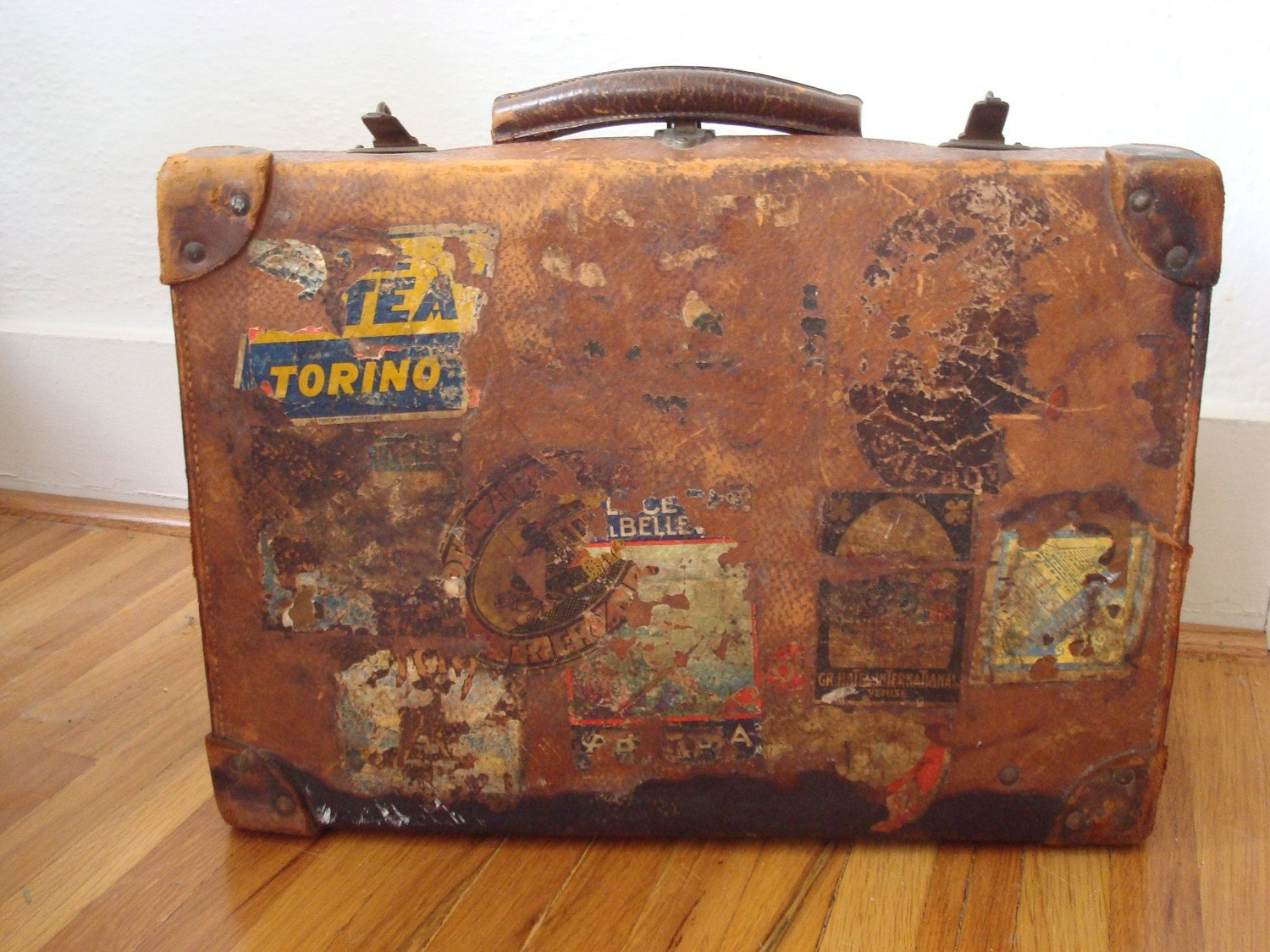 Antique leather steamer suitcase with luggage labels prop for What to do with vintage suitcases
