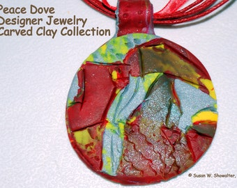 Lovely hand carved yellow, red, blue, brown and green Sculptural Clay Designer Pendant, 1 1/2 in., 18 in. necklace, 2 in. ext.
