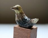 small yellow black ceramic bird 3 on a wood block