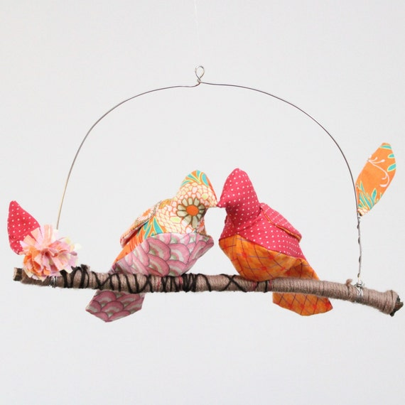 Little lovebird steals a kiss - fabric mobile on yarn wrapped branch in tangerine orange, cherry pink, and a touch of white