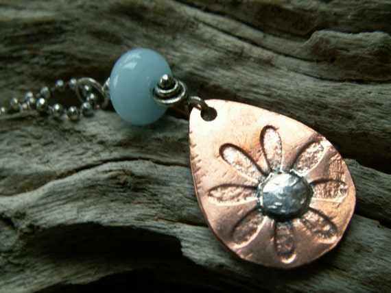 Rustic Bloom-:-Daisy embossed copper teardrop pendant.Pale blue glass bead,unique silver bail,on silver bead chain.Flower-Nature