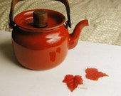 red-orange vintage tea pot with wooden handle.