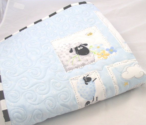 Black and White Sheep Adorn a Pale Blue Baby Quilt