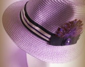 Fedora summer hat for women in wisteria variegated straw with black/warm grey grosgrain ribbon and half moon purple feathers.