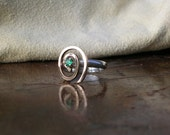 silver band with gold spiral and emerald