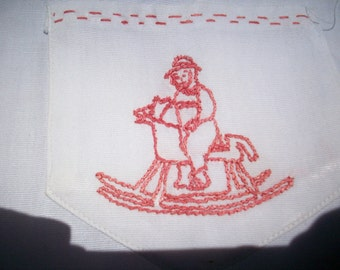 Antique child's garment with a cute rocking horse