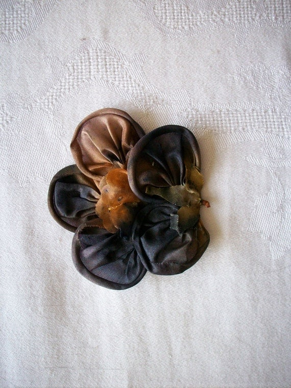 ribbonwork flower in black with touches of amber