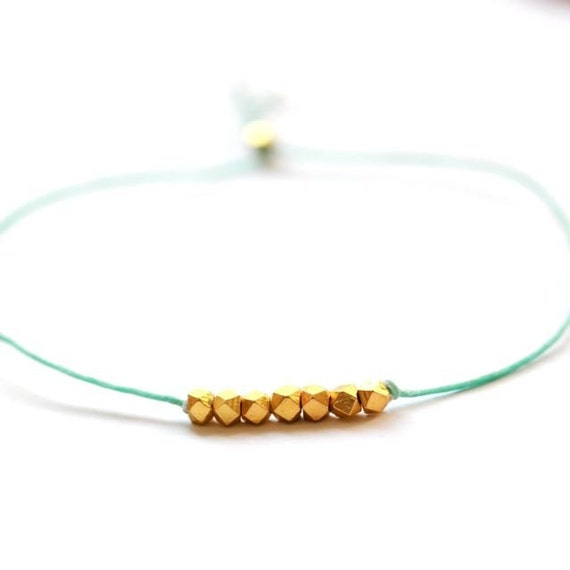 Wish bracelet beaded on sage green waxed linen cord with gold nuggets
