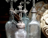 Cross Bottle --Medieval style cross of aged pewter atop an antique bottle of pale and wavy aqua glass
