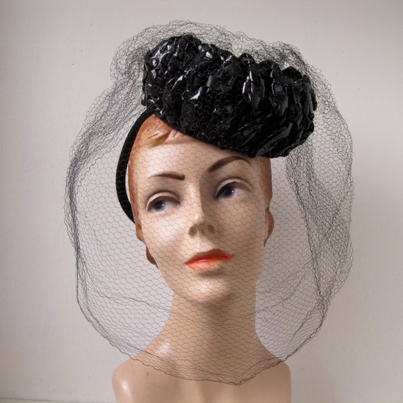Made in the USA The Rose Veil Wool Felt Coachman Top Hat by Toucan is a gorgeously feminine top hat style for women. Made of classic wool felt, this top hat features a stout crown accented with a two-pleat satin hat band, veil and oversized rose details at the side.