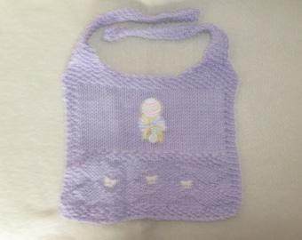 a lilac handknitted babys bib