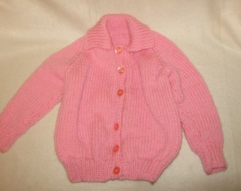 a chunky knit childs pink sweater