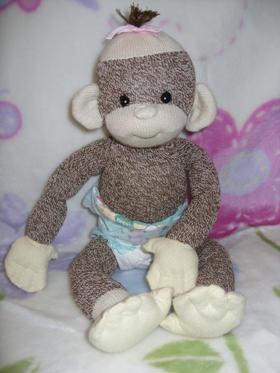 This Monkey Costume features a plush brown monkey jumpsuit with attached footies, monkey tail, and light brown tummy. The matching plush hood has a smiling monkey face on the top with a fluffy tuft of hair, ears, and a large opening for your baby's face.