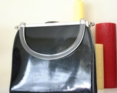 Sleek mid century black shiny patent purse with clear lucite handle