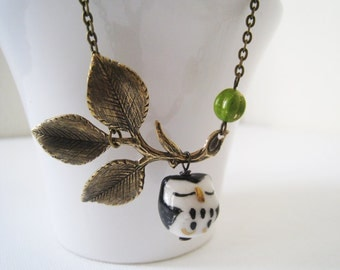 Black Owl Necklace. black owl on leafy branch in antique brass