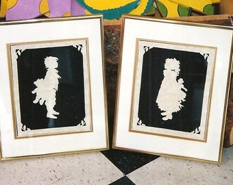 Old-fashioned parchment scherenschnitte paper-cutting boy and girl set