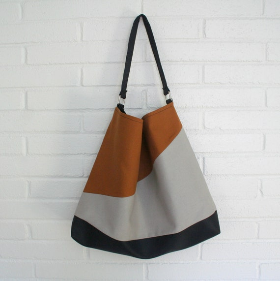 Angled style hobo bag in Black, tan and grey.