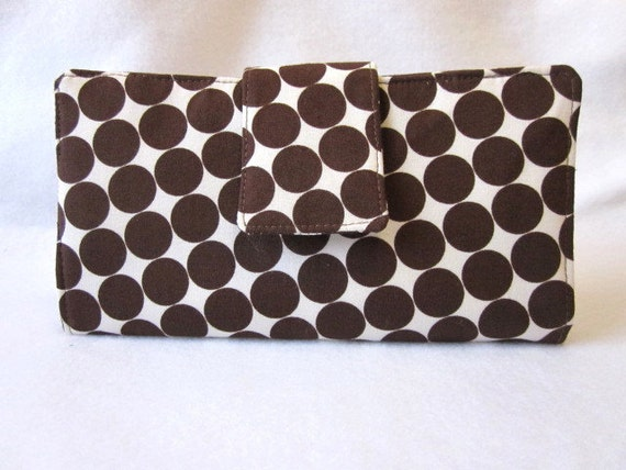 Wallet with brown dots on off white background a modern look.