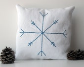 Small white cotton decorative pillow with blue embroidered snowflake