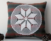 Small red, blue and green striped decorative pillow with white doily