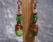 Green glass tear drops wrapped with copper wire with faceted glass beads above.