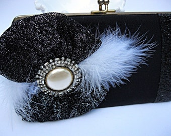 Glittery black and satin vintage clutch embellished with feathers and rhinestone pin