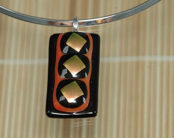 A burnt orange and gold fused glass pendant.