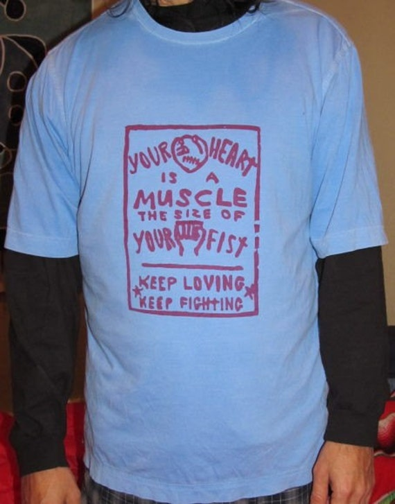 Your Heart is a Muscle the Size of Your Fist, Red on Light Blue T Shirt, Large