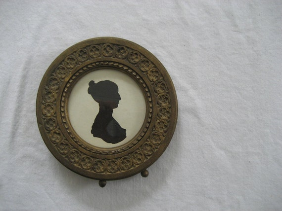 antique silhouette of woman in ornate carved round wooden frame