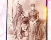 Antique photo cabinet card of serious young couple, girl with tight dress