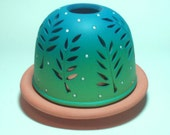 electric night light shaded from deep teal to light green, surrounded with fern cut outs.